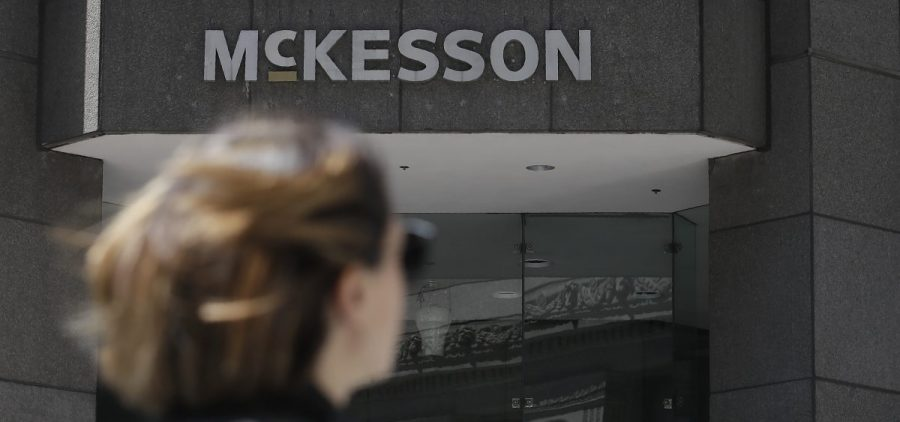 A pedestrian passes a McKesson sign on an office building in San Francisco.