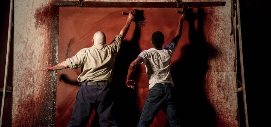 two men from the back painting life size canvas red
