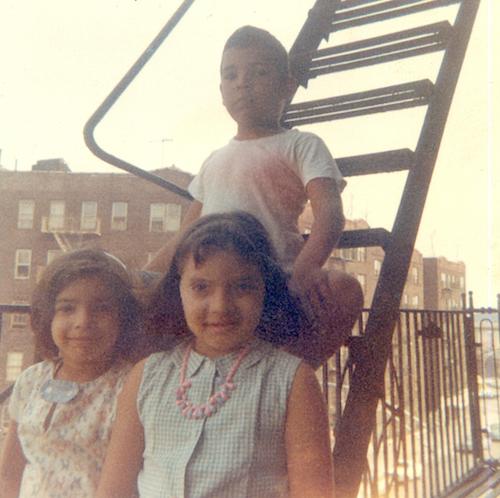 three children sitting on inncer city fire escape