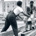Men stacking 4 by 4s in inner city
