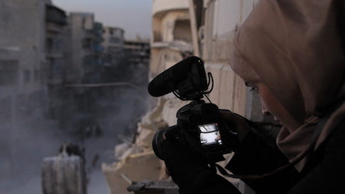 femiale videographer looking at viewfinder in Syrian warzone