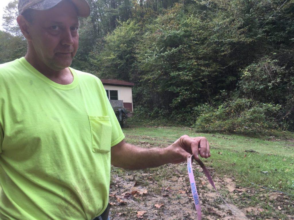 Elvis Thacker holds material swept down from the neighboring mine.