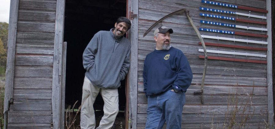 TWO MEN STADING IN FRON OF OLD WOODEN SHED