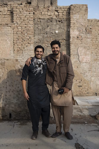 Two men in front of stone bulding in middle east