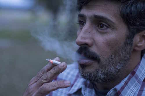 Image of middle eastern interpreter smoking cigarette