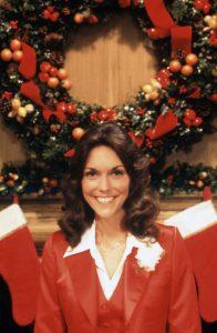 Karen Carpenter standing in front of Christmas wreath