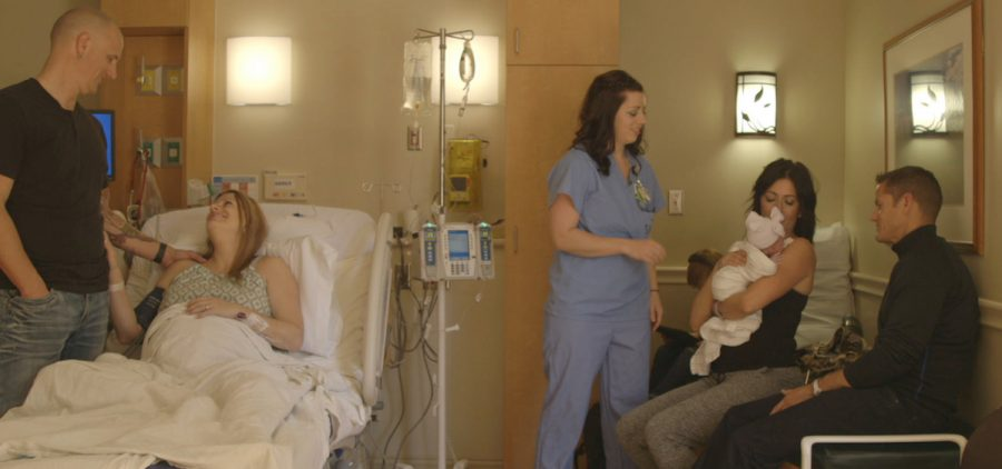 family in delivery room after having baby