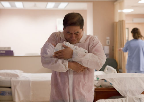 new father weeping holding baby