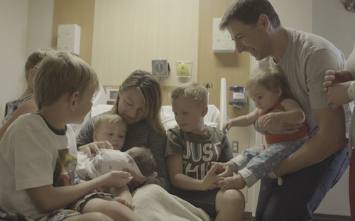 mom in hospital bedwith new baby and six siblings