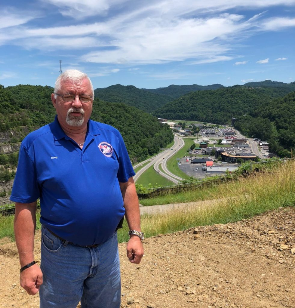 Doug Tackett, head of Pike County's emergency management division, stands at the top of the Pikeville Cut-Through in June. Officials cut a mountain in two in the 1970s, rerouting a river to avoid flooding. It was one of the largest land movements in the Western hemisphere.