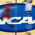 The NCAA logo stands at mid-court during the 2015 NCAA Division I men's basketball tournament, an event that annually rakes in significant revenue for the organization. In a major reversal Tuesday, the governing body signaled it would allow compensation for college athletes.