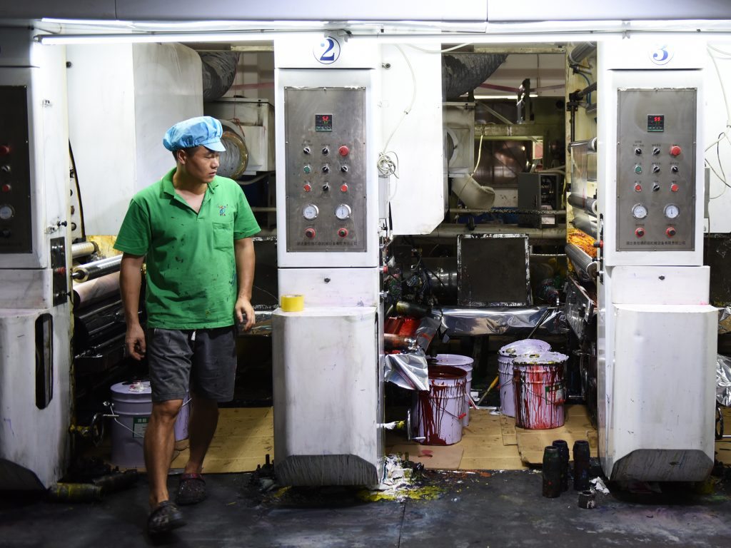 Workers in green polo shirts and blue caps monitor machines making plastic products at the Dongguan Fangjie Printing and Packaging Company.
