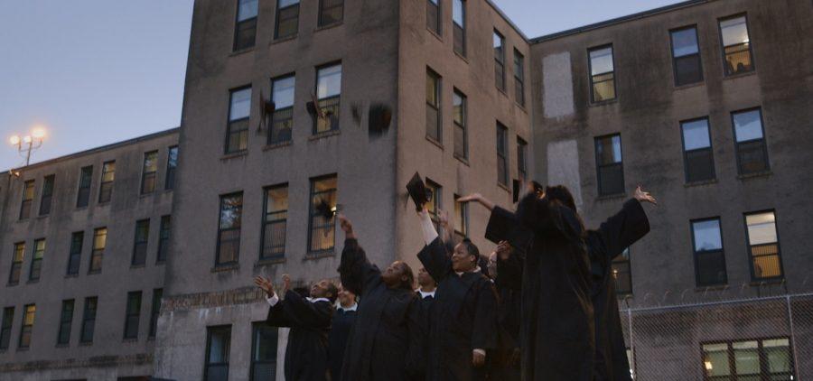 college graduates tossing caps in front of prison