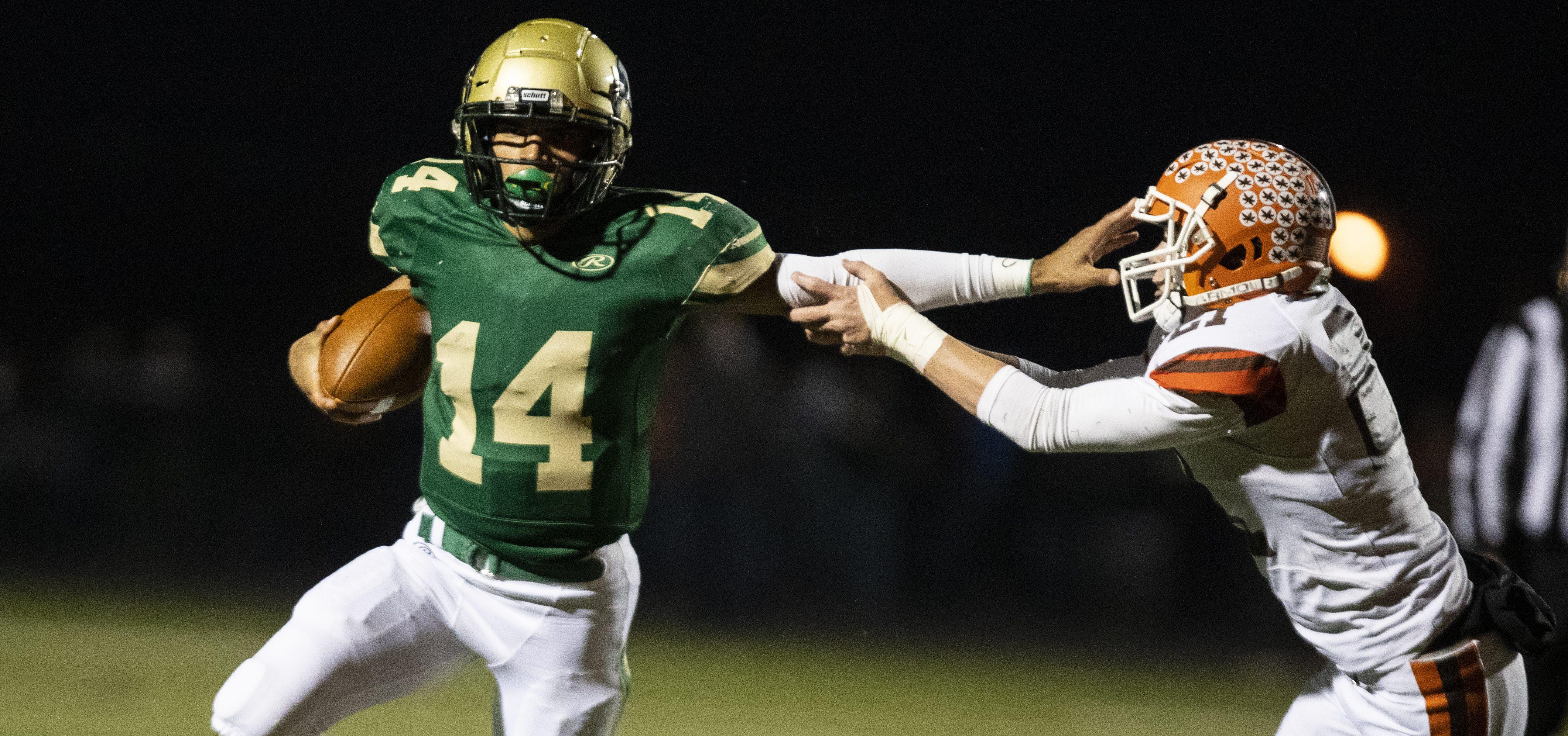 Athens quarterback Joey Moore stiff arms a Nelsonville-York players (Yukia/WOUB.