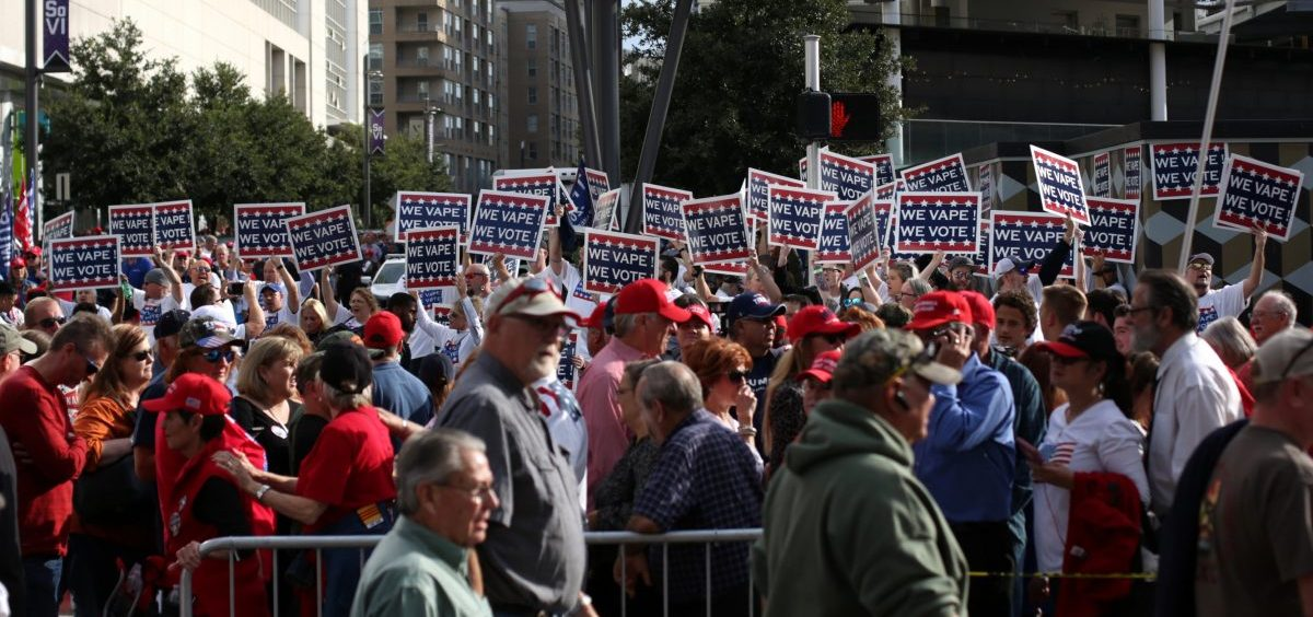 """Attendees hold """"We Vape, We Vote"""" signs ahead of a Trump rally last month in Dallas. The politics surrounding vaping and industry pushback against regulation appear to have derailed the Trump administration's plan to ban the sales of many vaping products."""