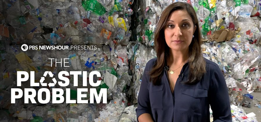 reporter standing in front of large plastic pile
