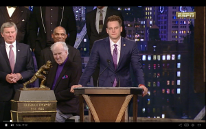 College football quarterback for LSU stands at podium to give speech after winning 2019 Heisman Trophy