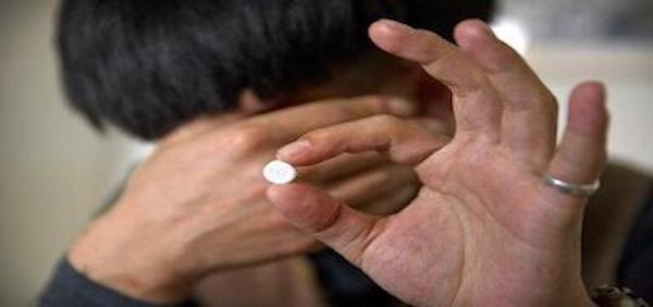 A person holds up a white pill to the camera. The person hides their fade in shame that the pills are addictive.