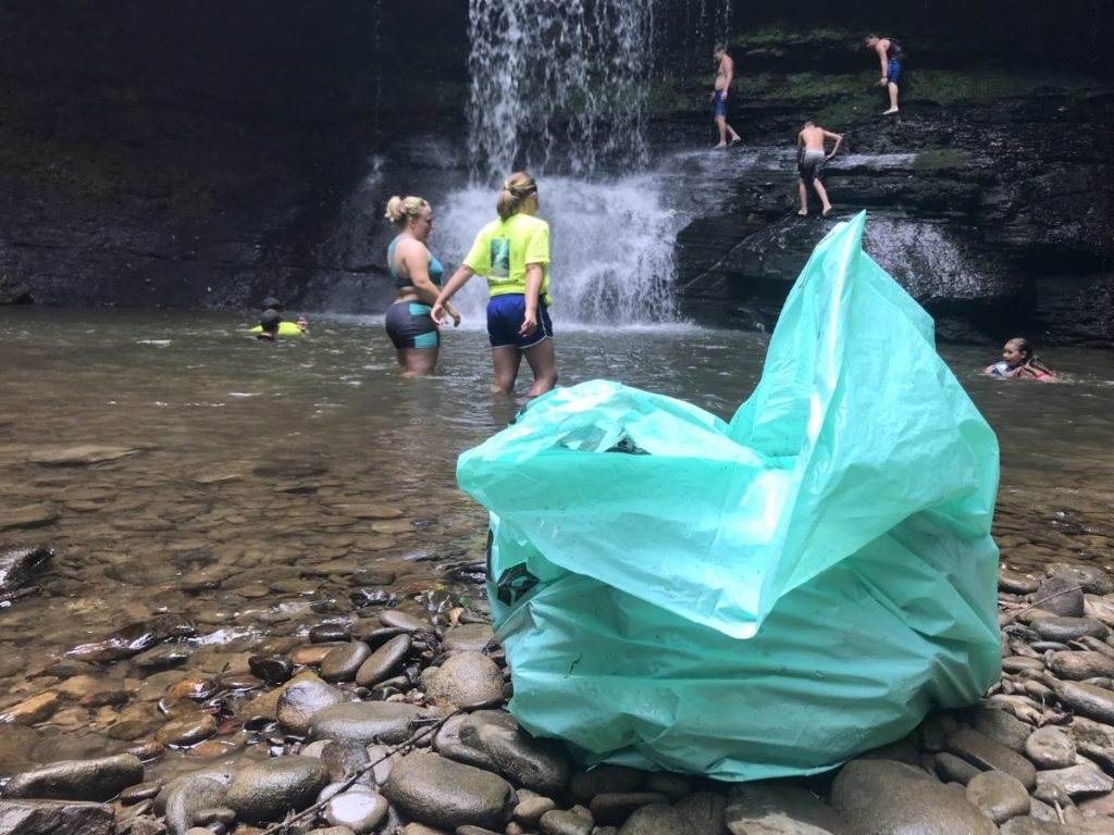 Volunteers swim in Peachtree Falls after cleaning up trash in the nearby creek.
