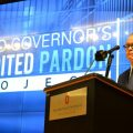 Gov. Mike DeWine, with Dean Christopher Peters of the University of Akron School of Law behind him, announces his expedited pardon process at Ohio State University's Moritz College of Law. Students from the two schools will help screen applicants.