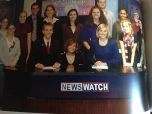 Shookman on WOUB news desk with group of students