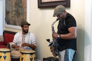 A man plays the sax while another plays hand drums