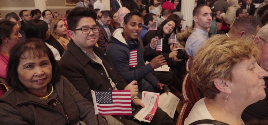 Newly sworn-in United States citizens are all smiles and waving flags during a naturalization ceremony
