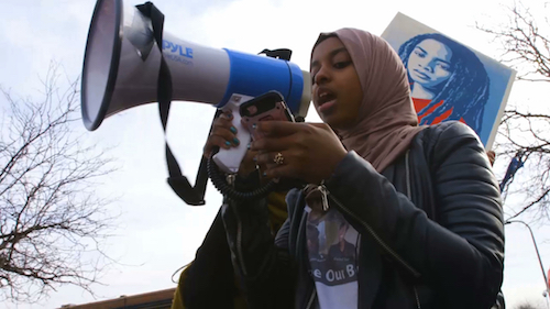 Woman speaking to protesters through bullhorn