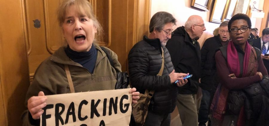 Demonstrators shouting chants outside of a House Public Utilities Committee hearing in the Ohio Statehouse.