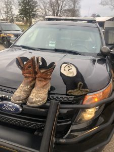 a pair of leather boots and knit mask displayed on the hood of a sheriff deputy's car