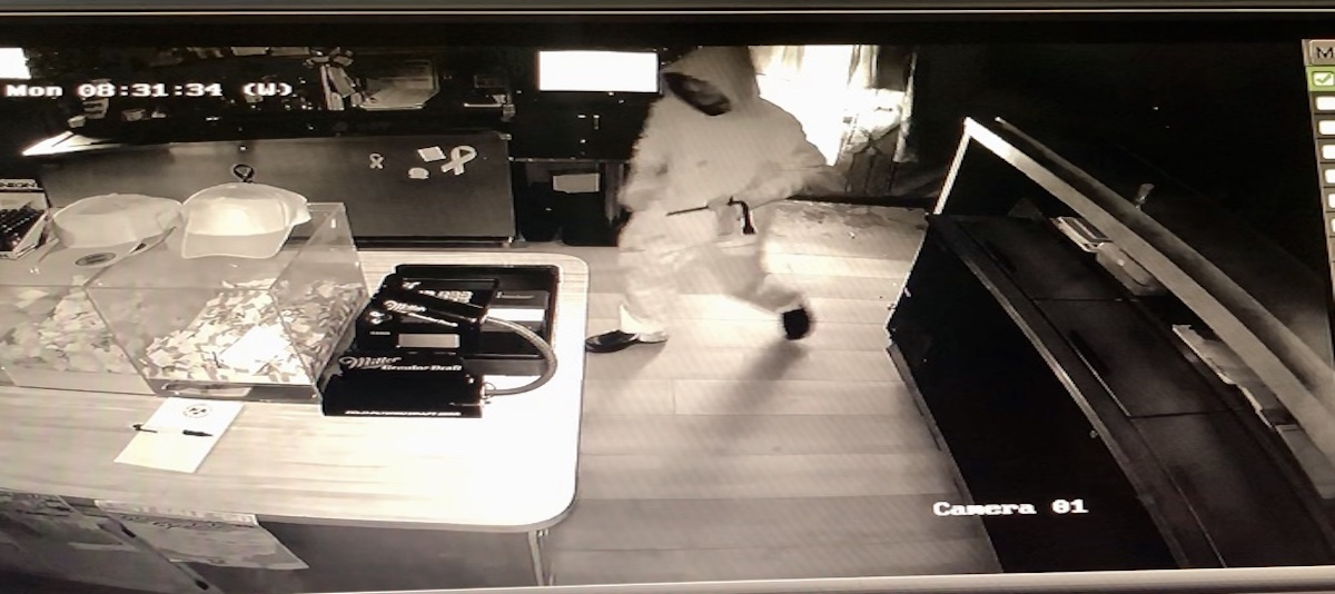 Black and white photo from surveillance video of a person inside of a restaurant