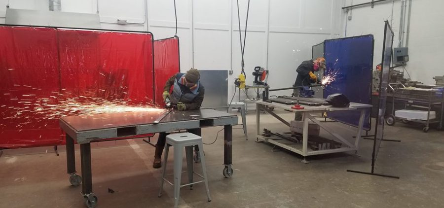People work in the open metal shop