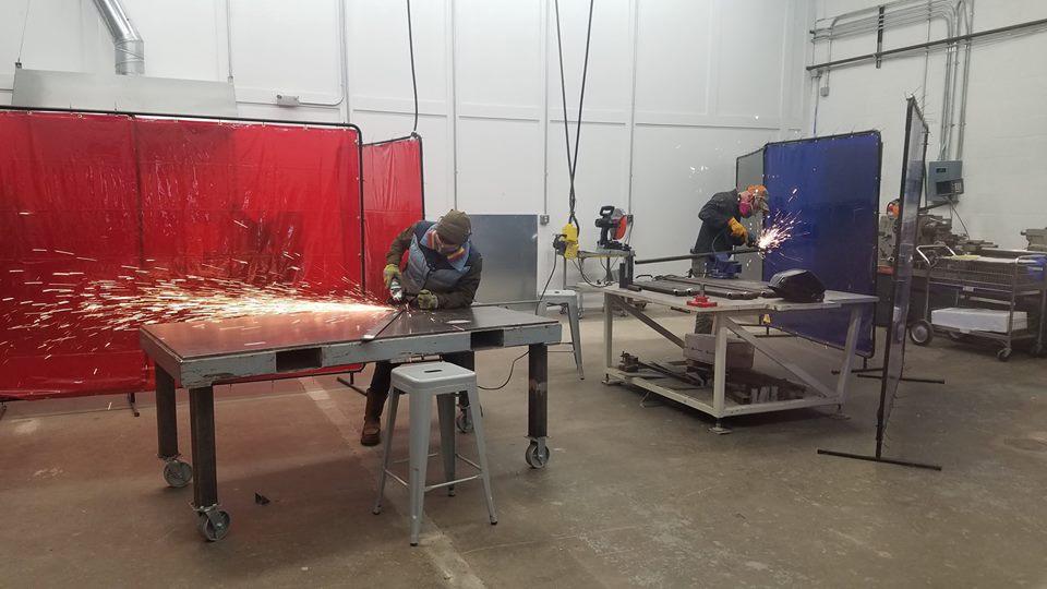 People work in the open metal shop