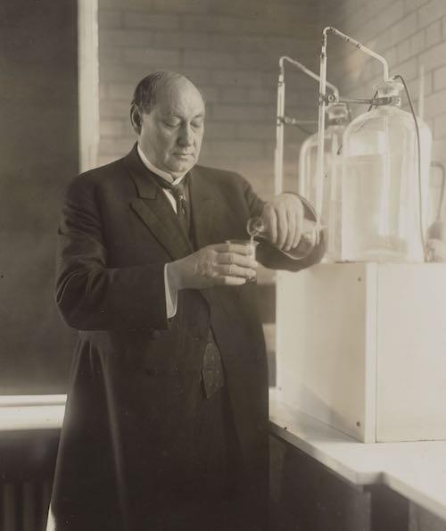 chemist poring from beaker to glass
