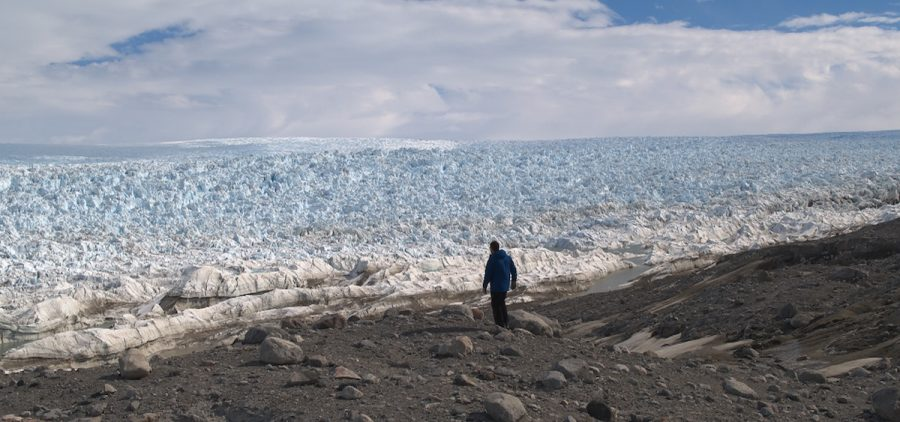 Man walking at edge of glacier