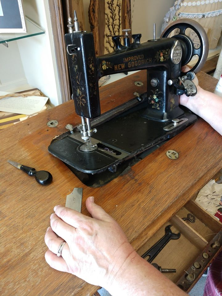 Someone operates a vintage sewing machine
