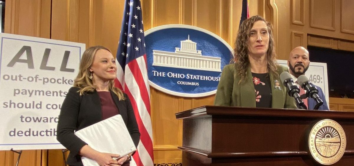 Rep. Randi Clites (D-Ravenna) speaks about the copay assistance bill sponsored by Rep. Susan Manchester (R-Waynesfield, left) and Rep. Thomas West (D-Canton). Clites' 17 year old son has hemophilia.