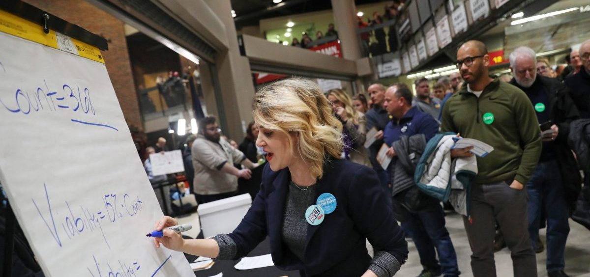 Precinct secretary Ari Fleisig writes in the number of people needed for a candidate to be viable at a caucus precinct site in Des Moines, Iowa on Monday night.