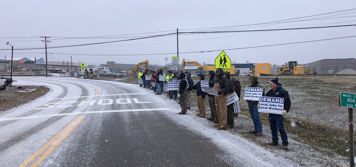 Workers with picket lines on the side of country road. There is a dusty of snow on the road