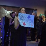 Supporters hold signs during the Night to Shine event