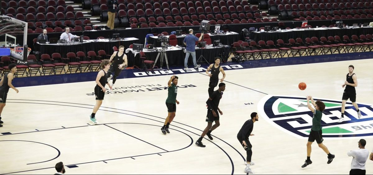 Ohio University basketball players warm up in an empty arena without fans before an NCAA college basketball game against Akron in the Mid-American Conference men's tournament, Thursday, March 12, 2020, in Cleveland..