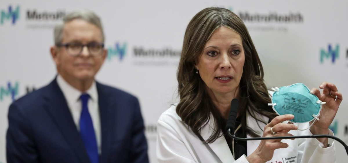 Ohio Department of Health Director Amy Acton holds up a mask as she gives an update at MetroHealth Medical Center Thursday, Feb. 27, 2020, in Cleveland, on the state's preparedness and education efforts to limit the potential spread of a new virus which caused a disease called COVID-19. Ohio Governor Mike DeWine, left, watches.