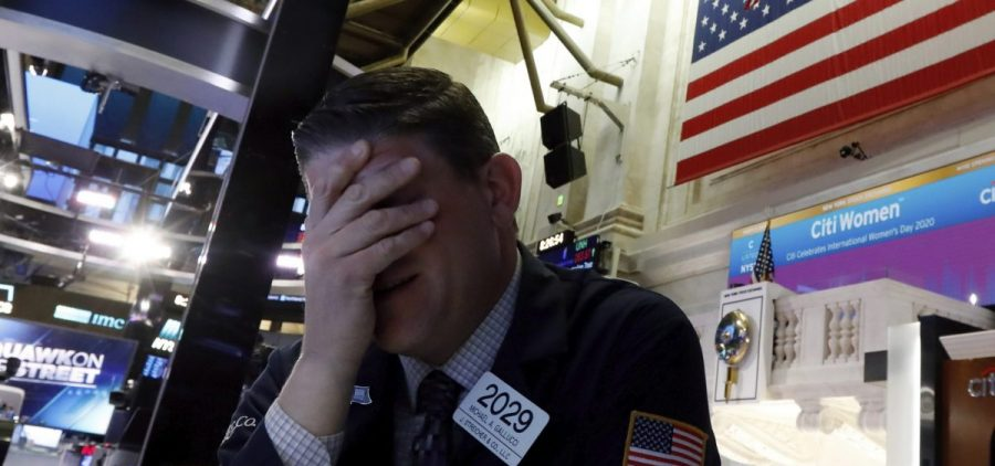 A trader reacts on the floor of the New York Stock Exchange on Monday. Major U.S. stock indexes plunged 7% before trading was temporarily halted.