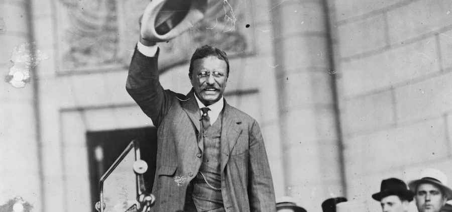 Theodore Roosevelt waves to a crowd.