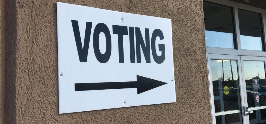 A voting sign points into a polling location