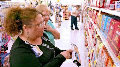 Shoppers looking at dietary info on food box