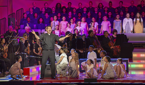 Priest with children's choir in the production of Mass