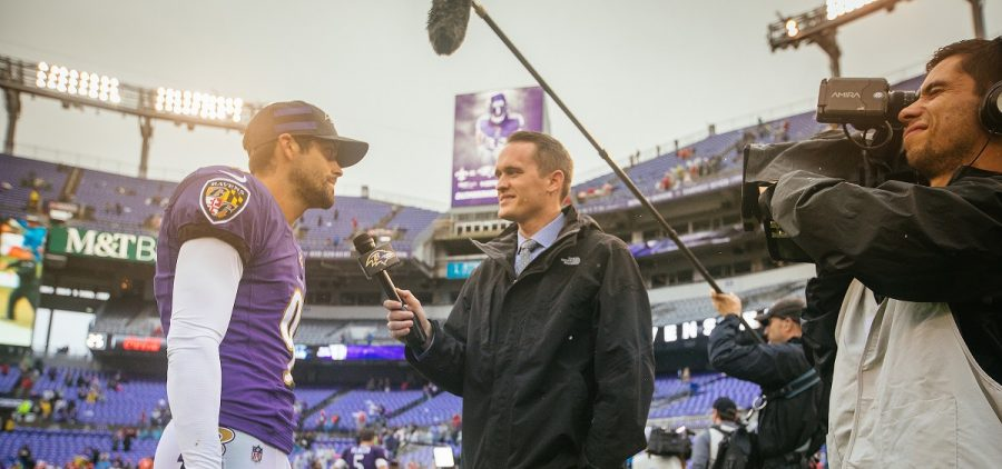 Downing interviewing player on field