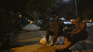 two women sitting in lawnchairs being interviews in the evening