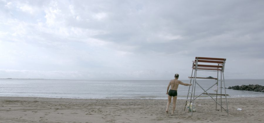 lone swimmer on beach at lifeguard stand